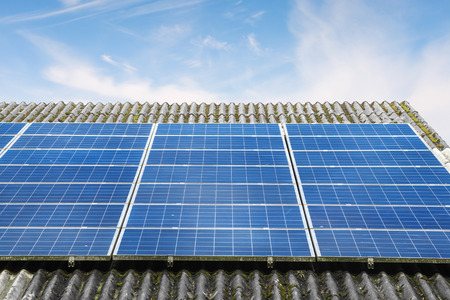 Solar panels in blue color on a roof in bright sunny weather under a blue sky Stok Fotoğraf
