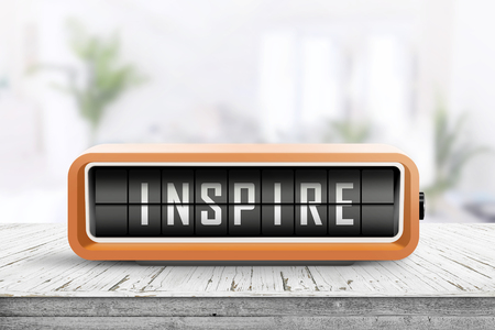 Inspire message on a retro alarm device on a wooden table in a bright room
