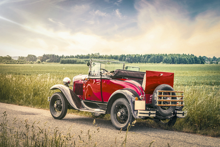 Antique red car on a road in a countryside landscape in the sunset Stok Fotoğraf