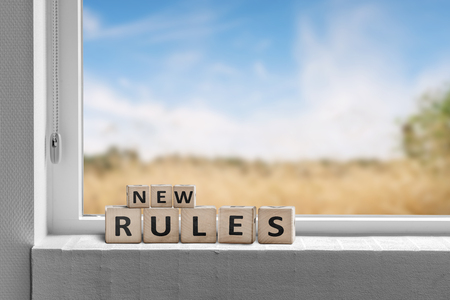 New rules sign in a window with a view to fields under a blue sky