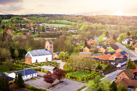 Village with a church in the morning sunrise seen from above