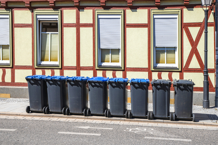 Garbage bins on the street outside an old house waiting for sanitation