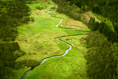 Curvy river running through a green area with fields and forest seen from above Stok Fotoğraf