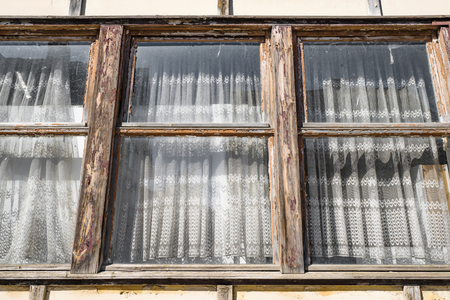Worn old windows with vintage curtains on an old building in a cottage