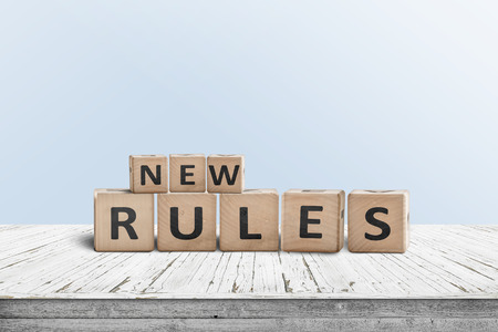 New rules sign made of wood on a desk in a room with a blue background