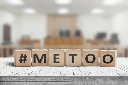 Metoo hashtag sign made of cubes on a wooden table in a courtroom