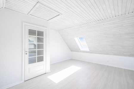 Bright room with the sun shining through a small window in a wooden apartment with a glass door