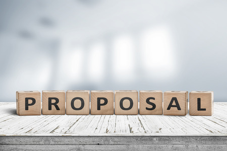 Proposal sign on a wooden desk in a bright office indicating a business suggestion