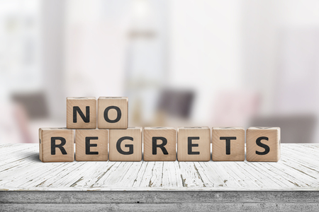 No regrets sign made with wooden blocks on a table in a bright room