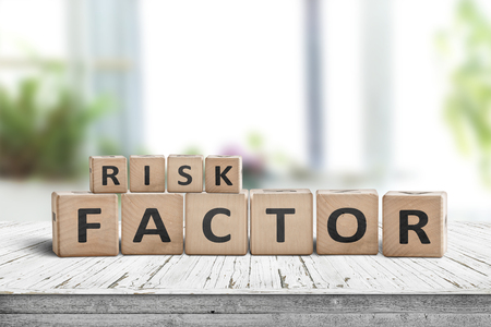 Risk factor sign on a wooden table in a bright living room in fresh daylight