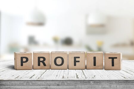 Profit sign in a bright room on a wooden table with white paint