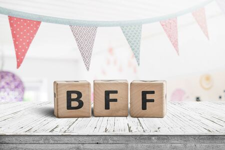 BFF greeting message made of wooden blocks with colorful flags hanging above