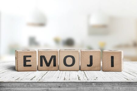 The word emoji on a wooden sign in a bright room on a white desk Фото со стока