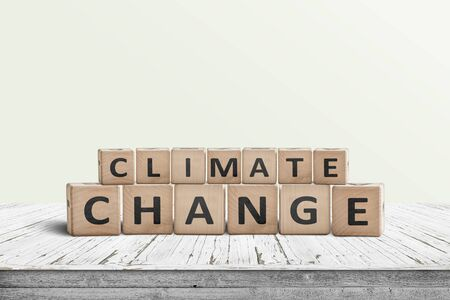 Climate change sign made of wooden cubes on a white desk