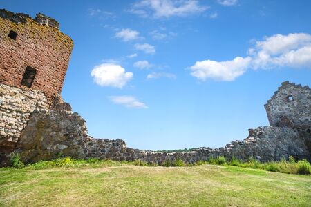 Castle ruin withh a stone wall under a blue sky with a green lawn in the front