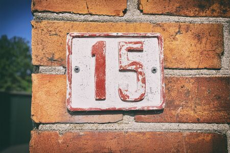 Street number 15 on a sign with pealing paint on a brick house in a street 스톡 콘텐츠
