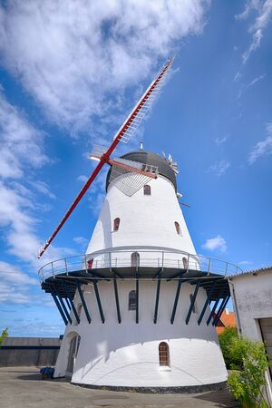 Old windmill rising up to a blue sky in the summer in white colors