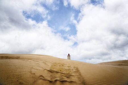 Lighthouse in the middle of a desert under a blue sky on a sandy dune Zdjęcie Seryjne