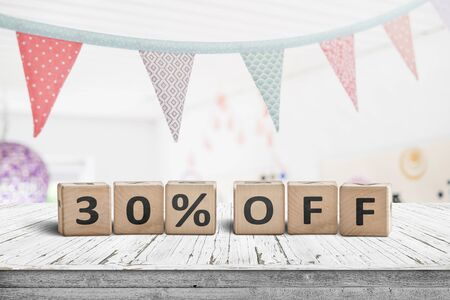 Special price 30 percent off promotion sign on a desk with colorful flags above