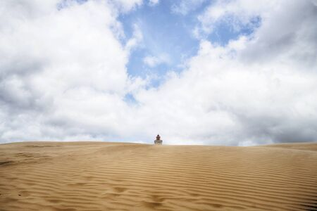 Lighthouse buried in a large sand dune under a blue cloudy sky in a desert Zdjęcie Seryjne