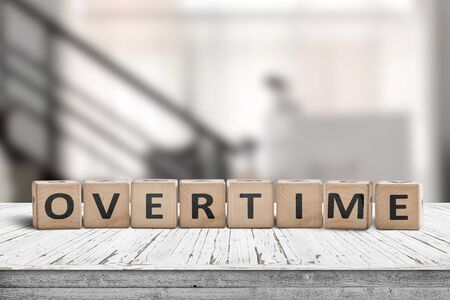 Overtime word spelled with wooden blocks in an office environment Foto de archivo