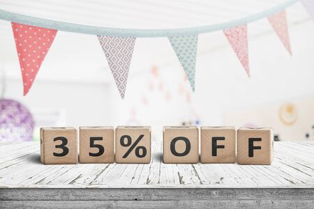 Special price 35 percent off promotion sign on a desk with colorful flags above