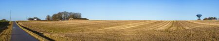 Rural panorama landscape with a dry field under a blue sky with a water tower on the right side 스톡 콘텐츠