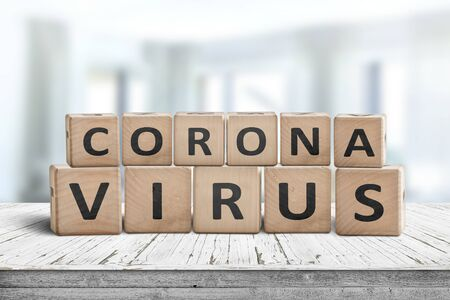 Corona virus alert message on a worn wooden desk i a bright environment