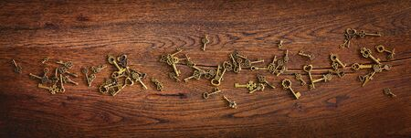 Magical bronze keys on a wooden oak surface in panorama format