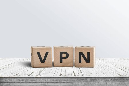 VPN word on wooden block sign in a bright room on a worn table 免版税图像