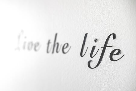 Live the life word phrase on a white wall written with black letters