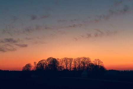 Sunset over a farmland with tree silhouettes ju8st before the sun is set