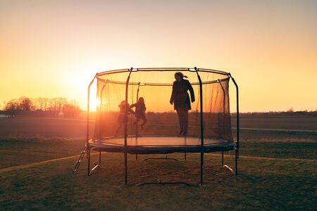 Trampoline on a lawn in the sunset with two kids and a young woman jumping and playing