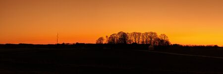 Warm countryside panorama sunset in a countryside landscape with tree silhouettes 免版税图像