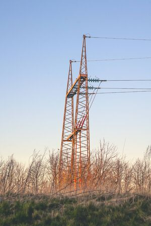 Red pylons in wild nature at dawn with a clear blue sky in the sunset