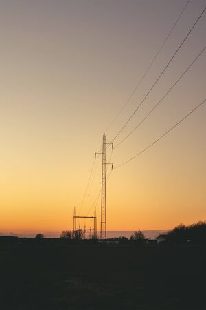 Electrical pylons at dawn in a beautiful sunset with a clear sky