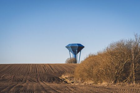 Blue water tower om a dry field with soil ready for the coming season