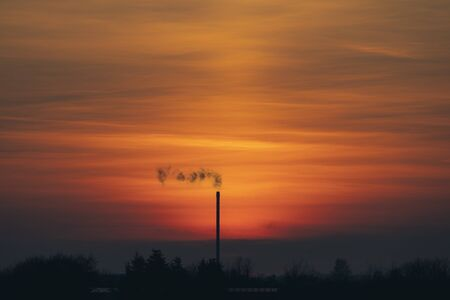 Smoke from a chimey in a beautiful sunset with industrial silhouettes 免版税图像