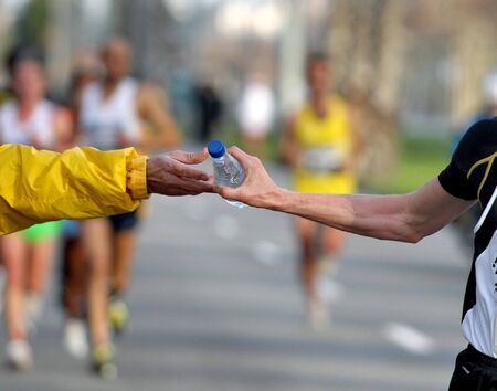 isotonic: Runner take a bottle of water on a long distance race