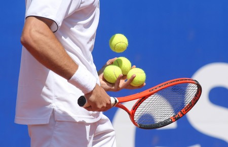 Tennis player checking balls on the racket