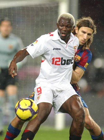 The Ivorian player Arouna Kone of Sevilla (L) fight with Chygrynskiy (R) during the 1/8 final King Cup match at the Nou Camp Stadium on January 5, 2010 in Barcelona, Spain.
