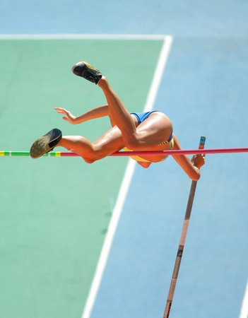An athlete attempts successfull a pole vault Stock Photo