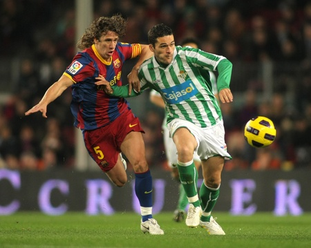 Puyol of Barcelona fight with Molina of Betis during the match between FC Barcelona and Real Betis at the Nou Camp Stadium on January 12, 2011 in Barcelona, Spain