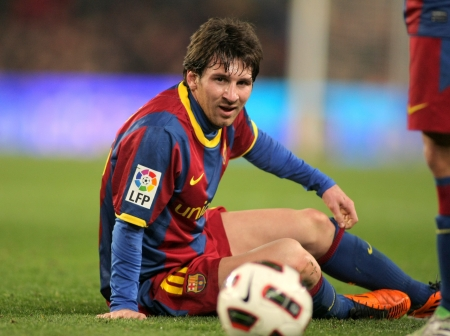 Messi of Barcelona fallen to the ground during the match between FC Barcelona and Athletic de Bilbao at the Nou Camp Stadium on February 20, 2011 in Barcelona, Spain