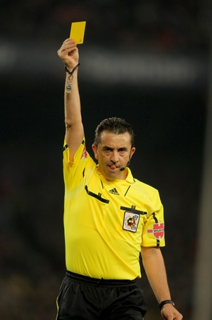 delivers: Referee Ramirez Dominguez delivers yellow card during the match between FC Barcelona and Athletic de Bilbao at the Nou Camp Stadium on February 20, 2011 in Barcelona, Spain Editorial