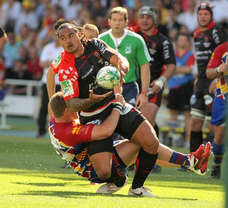 Toulonss Christian Loamanu is tackled by Perpignans player during the Heineken European Cup quarter-final match USAP Perpignan against RC Toulon at the Olympic Stadium in Barcelona, on April 9, 2011