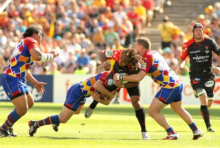 toulon: Toulonss Gabiriele Lovobalavu is tackled by Perpignans players during the Heineken European Cup quarter-final match USAP Perpignan against RC Toulon at the Olympic Stadium in Barcelona, on April 9, 2011 Editorial