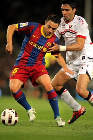 xavi: Xavi Hernandez of Barcelona fight with Nekounam of Osasuna during the match between FC Barcelona and Osasuna at the Nou Camp Stadium on April 23, 2011 in Barcelona, Spain