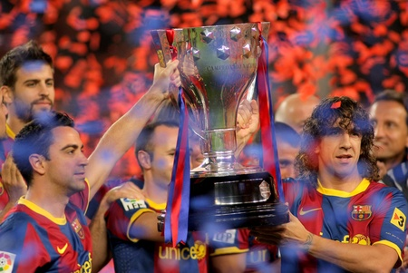 Xavi Hernandez and Carles Puyol of FC Barcelona hold the La Liga trophy after the match between Barcelona and Deportivo La Coruna at Camp Nou Stadium on May 15, 2011 in Barcelona, Spain