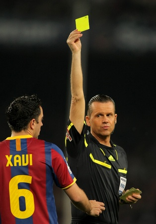 cf: Spanish Referee Muniz Fernandez delivers yellow card to Xavi Hernandez during the match between FC Barcelona and Getafe CF at the Nou Camp Stadium on March 19, 2011 in Barcelona, Spain